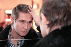 Junger Mann schaut im Spiegel Stockbild