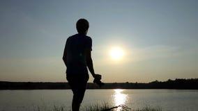 Junger Mann schießt ein goldenes sunpath bei Sonnenuntergang in SlomO stock video footage