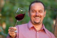 Junger Mann schmeckt Rotwein Stockbild