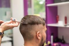 Junger Mann schneidet Haar im Friseursalon Stockfoto