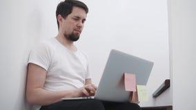 Junger Mann schreibt auf einem Laptop, der in einem Haus sitzt und steht im Internet in Verbindung stock video footage