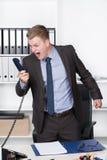 Junger Mann schreit in das Telefon Stockbilder