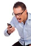 Junger Mann schreit an seinem Handy Stockfoto
