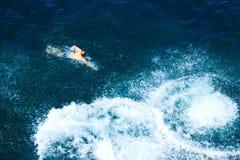 Junger Mann schwimmt im Meer Stockfoto