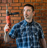 Junger Mann in seinem 30s, das eine rote elektrische Bohrmaschine hält Stockfotos