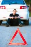 Junger Mann sendet die sms, die durch ein weißes Auto sitzen Lizenzfreie Stockfotos