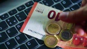 Junger Mann setzt Eurorechnungen und Münzen auf die Tastatur eines Laptops stock video