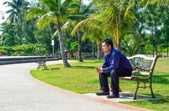 Junger Mann sitzen auf der Bank Stockfoto