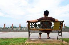 Junger Mann sitzen auf der Bank Stockfotografie