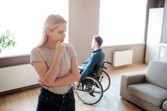 Junger Mann sitzen mit speziellem Bedarf sitzen auf Rollstuhl und Blick auf Fenster Frauenstand in der Front und denken Argumenti stockbild