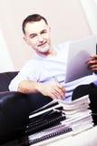 Junger Mann, sitzend auf der Couch nahe bei und Arbeit. Stockfotografie