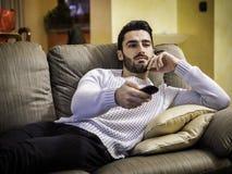 Junger Mann sitzendes aufpassendes Fernsehen mit Fernbedienung lizenzfreie stockfotos