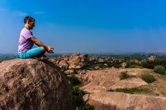 Junger Mann sitzt auf dem Berg mit schöner Ansicht Stockbild