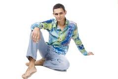 Junger Mann sitzt auf einem Fußboden lizenzfreie stockfotos