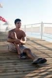 Junger Mann sitzt auf einem Pier nahe dem Meer Lizenzfreies Stockbild