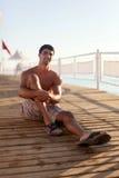 Junger Mann sitzt auf einem Pier nahe dem Meer Lizenzfreie Stockfotos