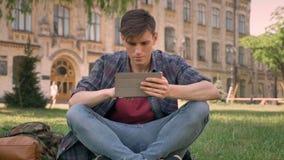 Junger Mann sitzt auf Gras im Park und passt Seiten im Internet auf der Tablette auf und passt an der Kamera auf, sich entspannen stock video footage