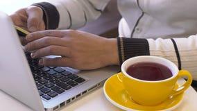 Junger Mann sitzt bei Tisch mit Laptop im Café stock footage