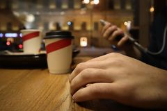 Junger Mann sitzt in einem Café und liest Mitteilungen im Telefon stockfotografie