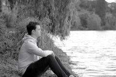 Junger Mann sitzt am Ufer mit einer Strickjacke und einer Haube stockbilder