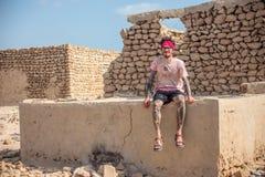 Junger Mann Smilling, der an den acient Ruinen des persischen Dorfs sitzt Stockbild