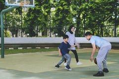 Junger Mann spielt Basketball mit seiner Frau und Sohn stockbild