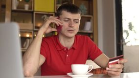 Junger Mann spricht am Telefon, das Kreditkarte hält stock video