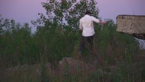 Junger Mann spricht telefonisch in den Dickichten des Grases stock video footage