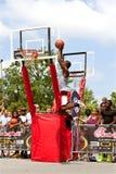 Junger Mann springt hoch in Basketball-Slam Dunk-Wettbewerb im Freien Stockfotos