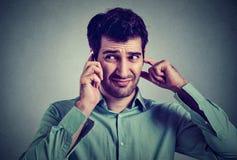 Junger Mann störte, frustriert durch jemand, das an seinem Handy hört lizenzfreie stockfotos
