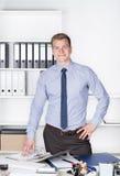 Junger Mann steht hinter dem Schreibtisch im Büro Stockfotos