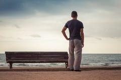 Junger Mann steht nahe alter Bank auf der Seeküste Lizenzfreies Stockfoto