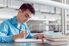 Junger Mann Student, der Kenntnisse an der Bibliothek nehmend lernt Lizenzfreie Stockfotos