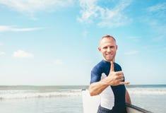 Junger Mann Surferporträt, das in camera das Shaka-Zeichengeste des Surfers berühmte wenn er kommend mit langem Brandungsbrett zu lizenzfreies stockfoto