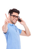 Junger Mann am Telefon, das Frieden zeigt Lizenzfreie Stockfotografie