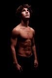 Junger Mann in toplessem oben schauen zur Leuchte Lizenzfreies Stockfoto