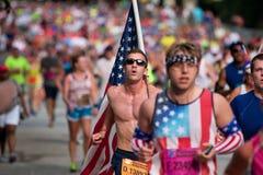 Junger Mann trägt große amerikanische Flagge in Rennen Atlantas 10K Lizenzfreie Stockfotos