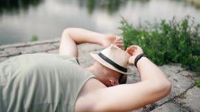 Junger Mann trägt Sommerkurze hosen, Strohhut und Sonnenbrille, entspannt sich auf einem Strand stock footage