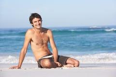 Junger Mann-tragendes Badebekleidungs-Sitzen Lizenzfreie Stockfotos