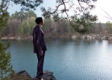 Junger Mann trifft Dämmerung auf Felsen durch den See Lizenzfreie Stockfotos