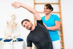 Junger Mann tut das Ausdehnen von Übungen mit Physiotherapeuten lizenzfreie stockbilder