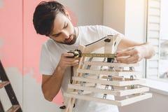 Junger Mann tut Wohnung repairment selbst zuhause Stockfotografie