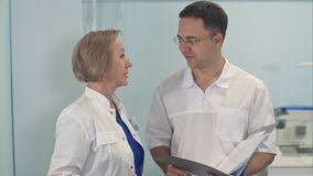Junger Mann und ältere Ärztin, die medizinischen Fall bespricht Stockfoto