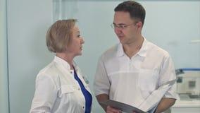 Junger Mann und ältere Ärztin, die medizinischen Fall bespricht stock footage