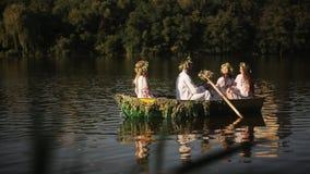 Junger Mann und drei schöne Mädchen in den Kränzen und in gestickten Hemden schwimmen in ein Boot auf dem Fluss slavic stock video