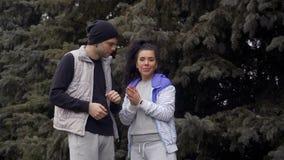 Junger Mann und Frau überprüft ihre Eignungsverfolger und -anfang, um zu laufen stock footage