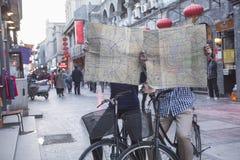 Junger Mann und Frau auf den Fahrrädern, die Karten halten. Lizenzfreie Stockfotografie