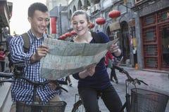 Junger Mann und Frau auf den Fahrrädern, Karte betrachtend. Stockbilder