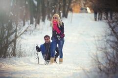 Junger Mann und Frau auf einem Schlitten Stockbilder