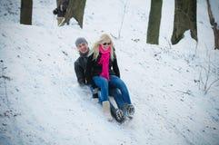 Junger Mann und Frau auf einem Schlitten Stockfotos